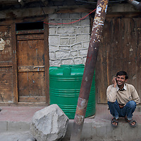 A man talks on his cell phone on a Kargil street