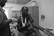 An MSF doctor treats a patient after he got injured by weapon at CBL Center of Bujumbura ( Center for injured people). @ Martine Perret . 24 October 2005.