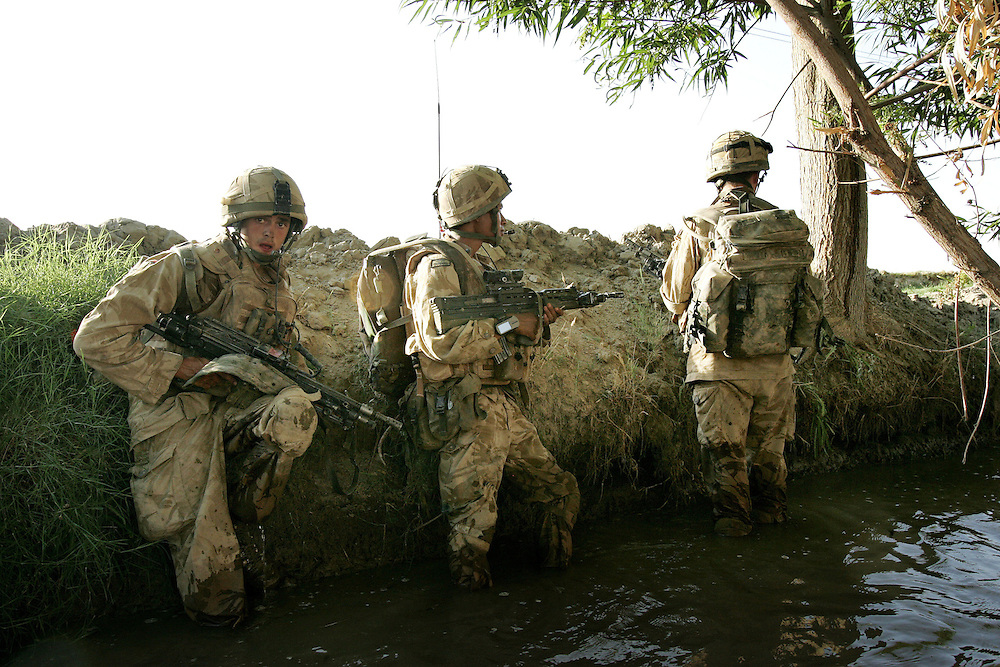29/06/07..Sangin Valley, Helmand, Afghanistan..Soldiers from A Company 1 Battalion Royal Anglians, known as 'The Vikings' shelter in an irrigation ditch after an RPG (Rocket Propelled Grenade) attack whilst conducting operations against the Taliban in the Sangin Valley, Helmand province, Afghanistan on the 29th June 2007...The soldiers made a Tactical Advance to Battle over night carrying just food, water and ammunition. At first light they moved on their objectives; a series of compounds, orchards and paddy fields. During the day they exchanged fire with the enemy on a number of occasions. 13 Taliban were killed, 1 British soldier and 3 Afghan troops were wounded.