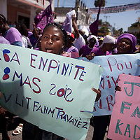 """Women's Day protestors carry signs that read """"Down with impunity. Long live the struggle of women workers"""" and """"Justice for victims of rape."""" (Photo by Ben Depp)"""