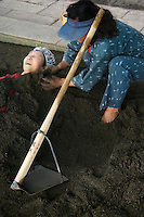 Japanese woman being buried in sand bath at Beppu, one of the few places in Japan where sand is used for spa treatments. Beppu's sand bath is conveniently located on Shoningahama Beach