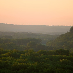 Haze and humidity cling to the bluffs surrounding the Mississippi River, lush with green summertime trees. The sun has just set, casting a warm glow over the scene.