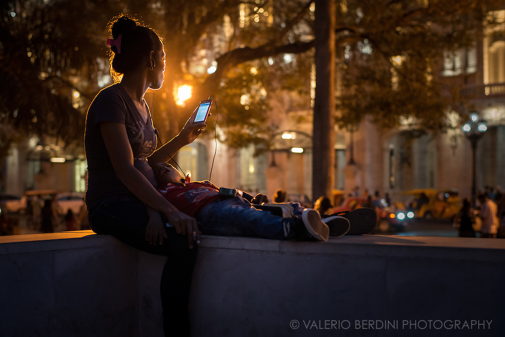 A mother with her child asleep, browse the internet in Parque Central in Havana, Cuba, on the afternoon of 28 December 2015. Her phone reads &quot;Pagina web no disponible&quot; (web page not accessible). Despite wi-fi is a great news for Cuba, the lines are not yet very reliable and the government does not allow every website and web service. This woman did not notice and was not aware of the photographer presence. This photo was not staged.<br /> <br /> This photo was published on the Guardian on 1 Feb 2016 http://www.theguardian.com/cities/gallery/2016/feb/01/havana-wi-fi-hotspots-revolution-street-life-in-pictures