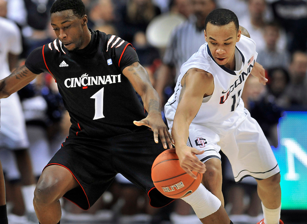 Connecticut's Shabazz Napier, right, steals the ball from Cincinnati's Cashmere Wright (1) in the first half of an NCAA college basketball game in Storrs, Conn., Wednesday, Jan. 18, 2012. (AP Photo/Jessica Hill)
