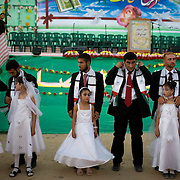 Hamas policemen stand with their own and their brides' younger sisters and cousins during a mass wedding for 55 policemen sponsored by the Hamas party in the Jabaliya camp in Gaza, Palestinian Territories on August 2, 2007.  Each groom was given $500 (U.S. dollars) from Hamas and $100 from Ismail Haniya as well as the free public wedding party. Hamas cements much of its' popularity by sponsoring community events such as this as well as providing free summer camps for kids, organizing trash pickups and food distributions across Gaza.