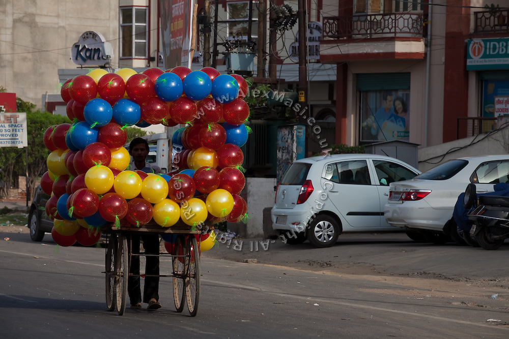 A balloon vendor is pushing his cart along the streets of Agra near the Taj Mahal.