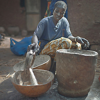 A dogon woman sitting in a courtyard pours millet into a calabash container, Dioundourou, Dogon Country, Mali.