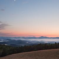 The moon starts setting early as the sun fades on the horizon of the Blue Ridge Mountains. Blue Ridge Parkway near E.B. Jeffress park, North Carolina