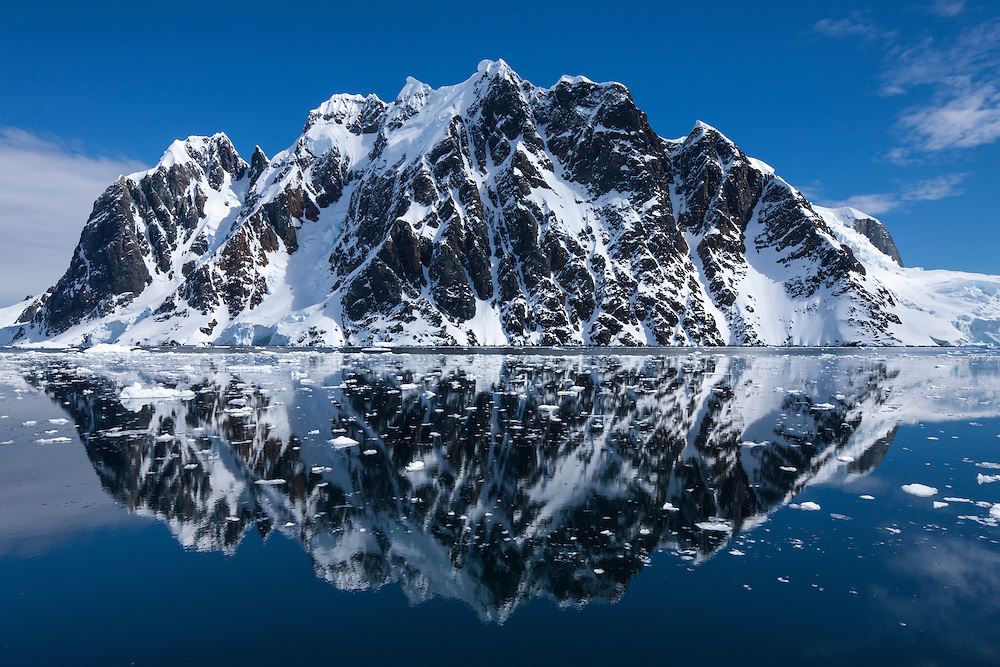 Antarctica, Mountain peaks reflected in calm waters of Lemaire Channel on sunny spring afternoon