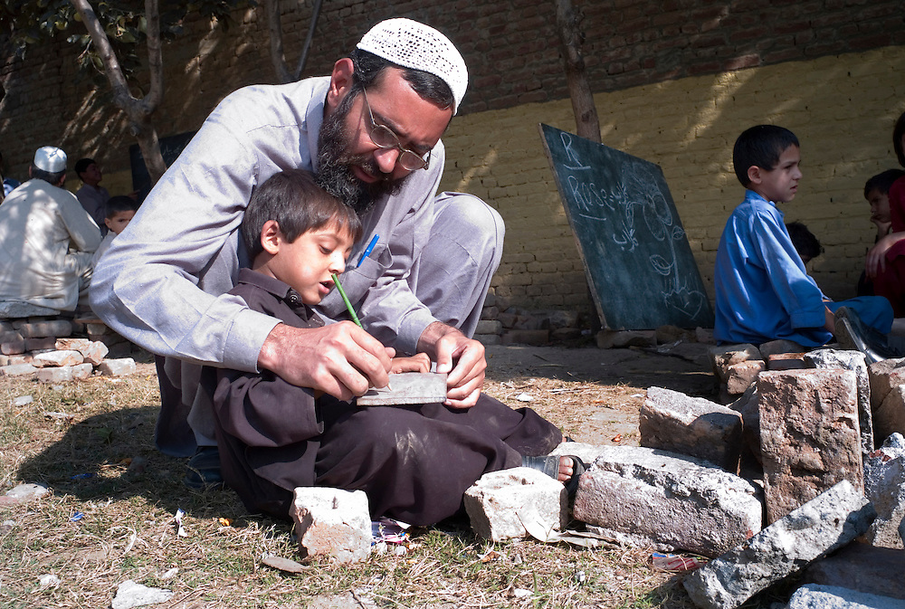 A teacher helps a young boy in a makeshift classroom in the grounds of their destroyed Nazarabad Government Boys School in SWAT...Rubble from the destroyed school has been used as improvised chairs in the shady areas underneath trees...Some pupils have returned to the makeshift open-air class rooms whilst others still fear the return of the Taliban and choose to stay away from lessons. .