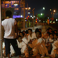 BEIJING, AUGUST - 2 : performers listen to their instructor before dress rehearsals inside the National Stadium.