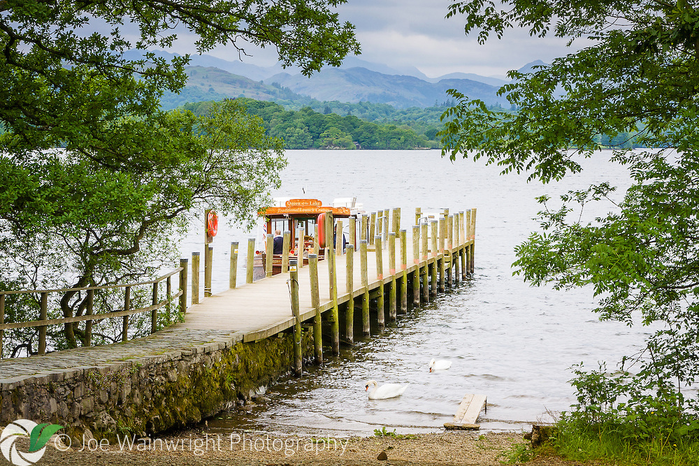 A boat departs from the landing stage at Brockhole, The Lake District Visitor Centre, near Windermere, Cumbria.