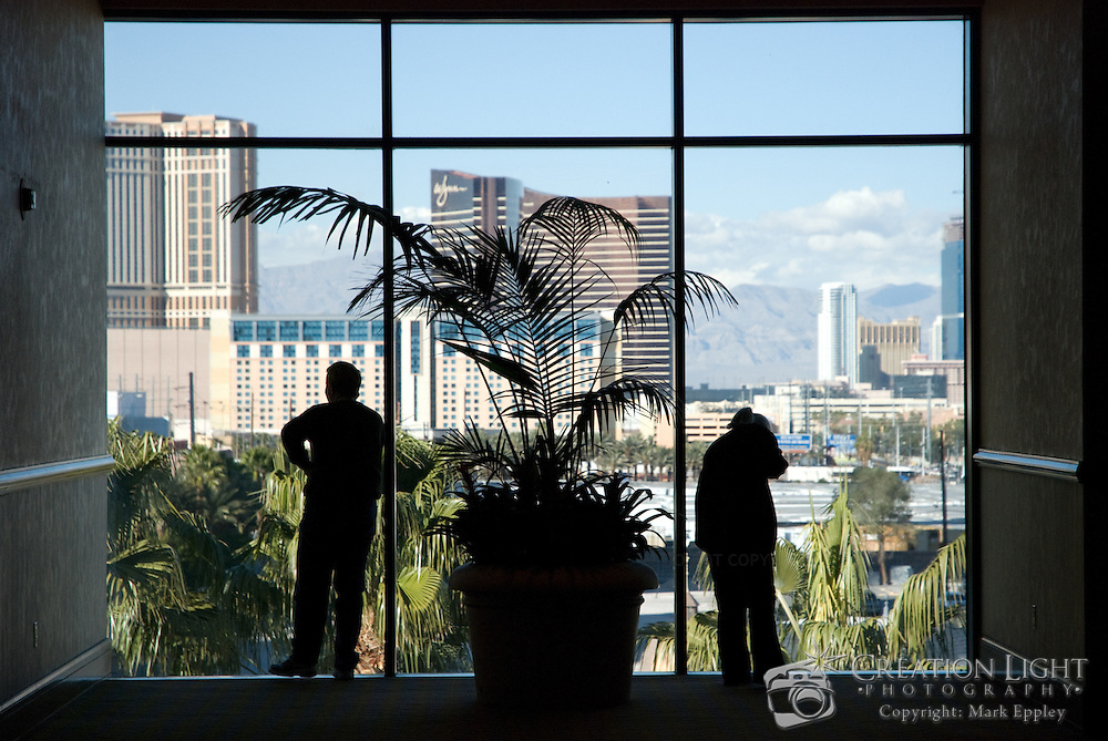While at a convention in Las Vegas, people during breaks would stand by windows talking on the cell phone.  The skyline of Las Vegas can be seen through the window.