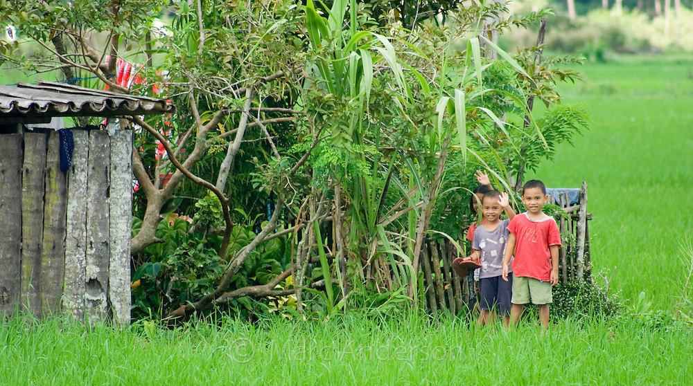 Two little boys outside their small traditional house, situated in a rice field, Bohol, Philippines.