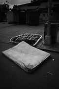 An abandoned mattress and box spring sits in the street in Bushwick, NY.
