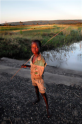 Hassan Dadi, 10,  who lost his arm after a lion ripped it off goes fishing with his friends near a swimming hole in the village of Usuru, Tanzania. Ami Vitale