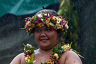 A girl dancer wearing a garland of flowers waits for the rain to ease before performing. Fatu Hiva, Marquesas islands, French Polynesia, South Pacific.