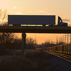 Two modes of transportation meet as a box truck passes overhead, with a loaded coal train on the tracks below.