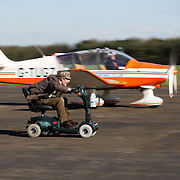 """COLIN FURZE RACING A PLANE ON HIS MOBILITY SCOOTER ON A AIRFIELD IN LINCOLNSHIRE... A plumber who built the world's FASTEST mobility scooter has now incredibly suped it up to race a PLANE...Colin Furze, 31, officially broke the world record with a remarkable speed of 71.59mph on the petrol-powered super scooter...Now after weeks of adjustments and fine tuning he has pitched the powerful machine against a propeller plane...""""I decided to change the gear ratio to help the scooter accelerate faster and thought it would be fun to test out against a plane,"""" he said...""""I was worried about how it would perform but amazingly it accelerated away from the starting line quicker than the plane and left it behind.""""..Colin spent nearly three months and £400 converting the machine which has a powerful 125cc motorbike engine hidden under the seat, five gears and twin exhausts...SEE COPY CATCHLINE  Mobility scooter in plane race"""