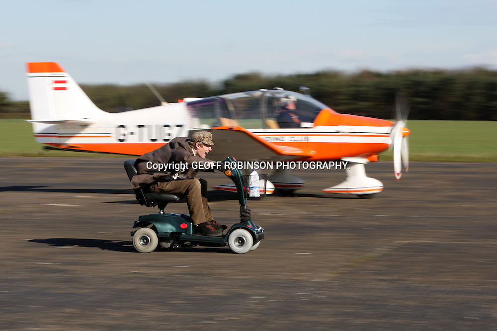 "COLIN FURZE RACING A PLANE ON HIS MOBILITY SCOOTER ON A AIRFIELD IN LINCOLNSHIRE... A plumber who built the world's FASTEST mobility scooter has now incredibly suped it up to race a PLANE...Colin Furze, 31, officially broke the world record with a remarkable speed of 71.59mph on the petrol-powered super scooter...Now after weeks of adjustments and fine tuning he has pitched the powerful machine against a propeller plane...""I decided to change the gear ratio to help the scooter accelerate faster and thought it would be fun to test out against a plane,"" he said...""I was worried about how it would perform but amazingly it accelerated away from the starting line quicker than the plane and left it behind.""..Colin spent nearly three months and £400 converting the machine which has a powerful 125cc motorbike engine hidden under the seat, five gears and twin exhausts...SEE COPY CATCHLINE  Mobility scooter in plane race"