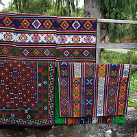 Asia, Bhutan, Bumthang. Textiles of Bhutan hanging outside shop.