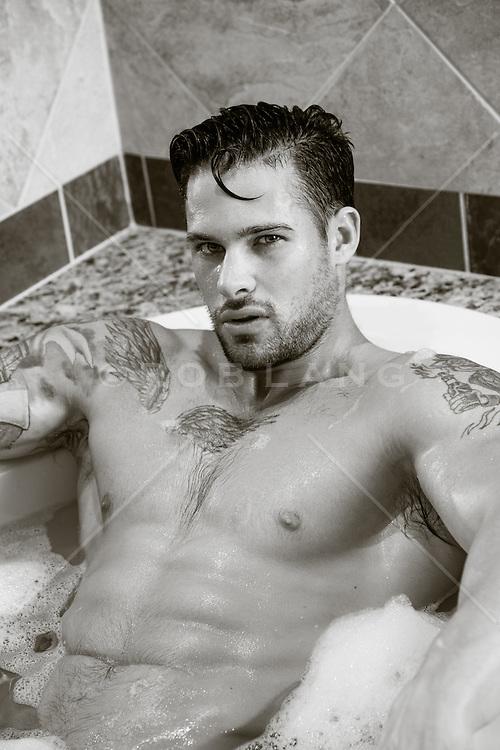 hot man with tattoos in a bathtub