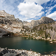 WY01828-00...WYOMING - Hiker at Suprise Lake in Grand Teton National Park. (MR# S1)