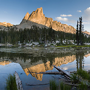 The pyramidal peak of El Capitan (9846 feet or 3001 elevation) reflects in the outlet stream of Alice Lake (Pettit Lake Creek) in Sawtooth Wilderness, Blaine County, Idaho, USA. The Sawtooth Range (part of the Rocky Mountains) are made of pink granite of the 50 million year old Sawtooth batholith. Sawtooth Wilderness, managed by the US Forest Service within Sawtooth National Recreation Area, has some of the best air quality in the lower 48 states (says the US EPA). Panorama stitched from 5 overlapping photos.