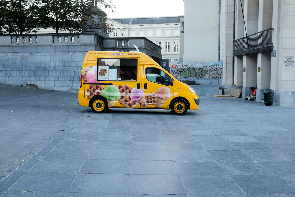 Selling waffles and ice cream, popular treats Belgium, this small yellow van sits on the plaza near the heart of Brussels.