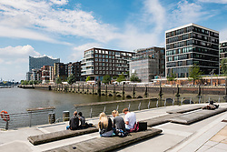 Young people sitting at Marco-Polo-Terrassen part of modern Hafencity property development in Hamburg Germany