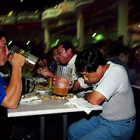 Drinking beer direct from pitchers in the main hall of the annual Tsingtao beer festival. The festival started in 1991, whilst the beer itself dates back to 1903 when the city was under German control...From China [sur]real © Mark Henley..