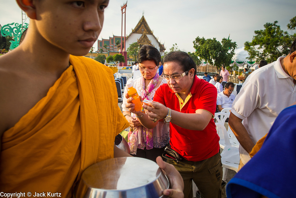 "01 JANUARY 2013 - BANGKOK, THAILAND:  A man presents an offering of juice to Buddhist monks during a special merit making ceremony at Bangkok City Hall New Year's morning. Many Thais go to Buddhist temples and shrines to ""make merit"" for the New Year. The traditional Thai New Year is based on the lunar calender and is celebrated in April, but the Gregorian New Year is celebrated throughout the Kingdom.     PHOTO BY JACK KURTZ"
