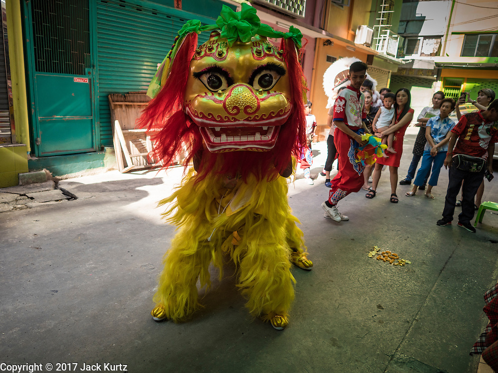 27 JANUARY 2017 - BANGKOK, THAILAND: Chinese Lion dancers perform at a fabric shop owned by a Thai-Chinese family in Bangkok on Chinese New Year. 2017 is the Year of the Rooster in the Chinese zodiac. This year's Lunar New Year festivities in Bangkok were toned down because many people are still mourning the death Bhumibol Adulyadej, the Late King of Thailand, who died on Oct 13, 2016. Chinese New Year is widely celebrated in Thailand, because ethnic Chinese are about 15% of the Thai population.       PHOTO BY JACK KURTZ