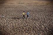 Two boys are walking inside one of the large evaporation pools once used by Union Carbide (now DOW Chemical) to dispose of its chemical wastewater, near the abandoned industrial complex in Bhopal, Madhya Pradesh, central India.