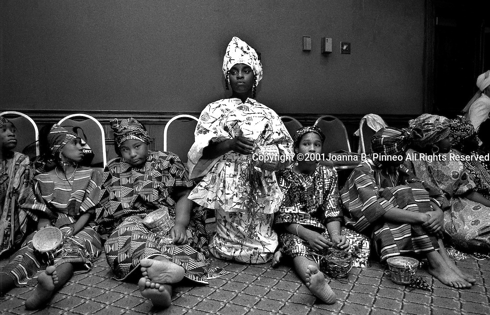 After being fitted with clothes of African design and heads wrapped, girls wait to practice the performance at the end of the program.<br />&quot;Black is the color of coal<br /> Black is the color of soil<br /> Black is night<br /> But Black is beautiful.&quot;<br /> From a poem by Sarah Poole.