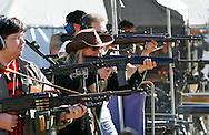 "This picture story:  Twice a year in a Kentucky ""holler"" fans of automatic weapons gather for a ""machine gun shoot"". Firing a wide variety of weapons from Uzi's to military .50 cal's they explode targets like junk cars and washing machines.....This picture: A variety of people with automatic weapons on the firing line at the Knob Creek Machine Gun Shoot near West Point, Kentucky April 9, 2005. Thousands of machine gun and military hardware enthusiasts attended the event held each year over weekends in the spring and fall."