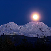 The full moon rises over Mount Rainier in this wintertime view from near Elbe, Washington. Mount Rainier, lit by alpenglow, is 14,411 feet (4,392 meters) tall, making it the highest point in Washington state and the highest volcano in the Cascade Range.