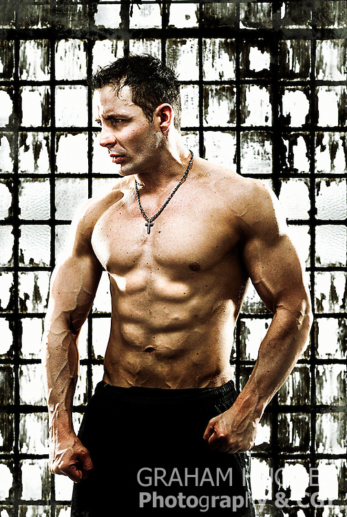 Muscular male with top off in front of glass wall