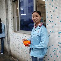 SHENZHEN, DEZ.12.2006: die 19 jaehrige Li Yanfang aus Henan vor der Kantine der Spielzeugfabrik, in der sie arbeitet.