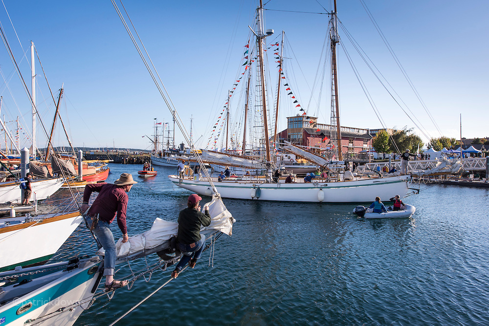Wooden Boat Festival: Guys work with their foresails as they watch the schooner Dirigo II come back into the harbor after the schooner race.