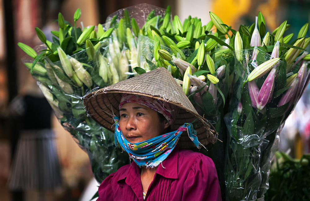 A flower seller in Hanoi, Vietnam making a delivery.