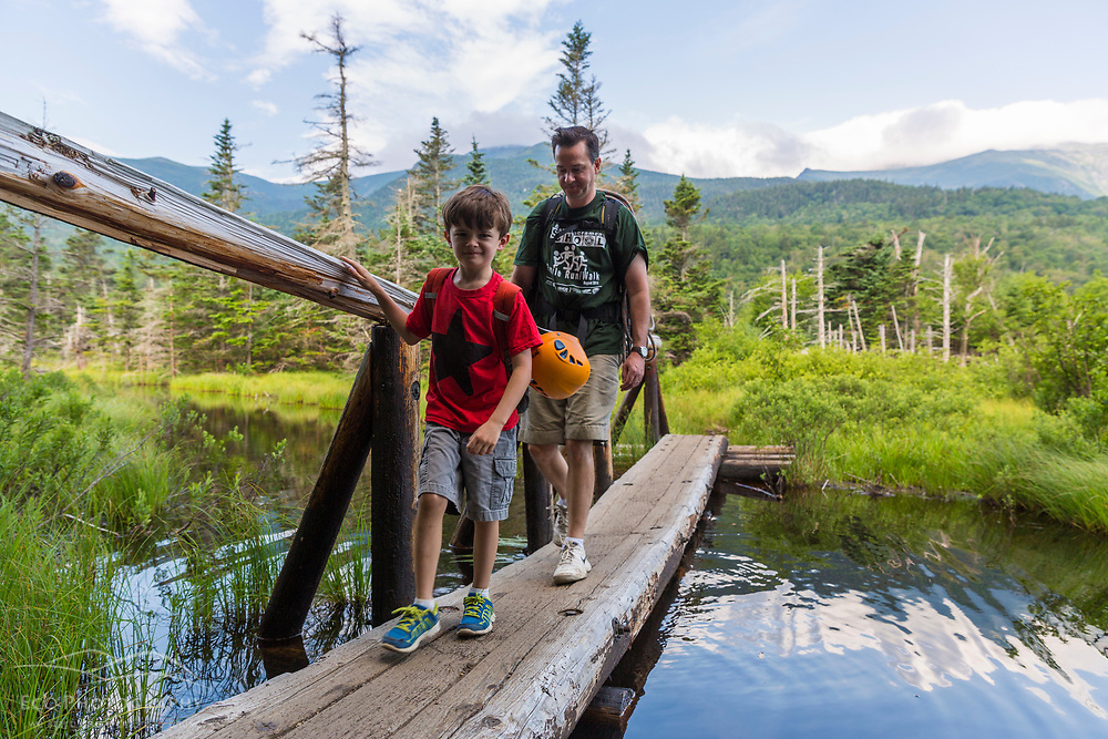 Writer Brad Tuttle and his son Nate hike over a bog bridge on the way to Square Ledge in New Hampshire's White Mountains.