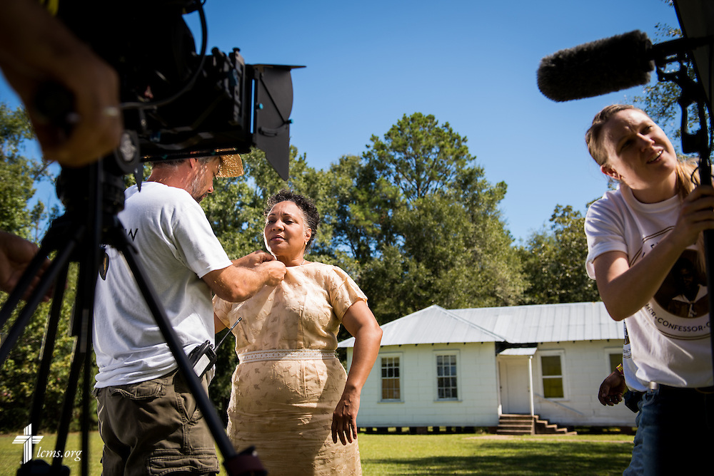 Actress Yvette Jones-Smedley, performing in the role of Rosa Young, receives a microphone from Audio Supervisor Mike Budzik as assistant Amanda Booth (right) helps with setup during filming of 'The First Rosa' documentary at Hope Lutheran Church on Wednesday, Sept. 24, 2014, near Selma, Ala. LCMS Communications/Erik M. Lunsford