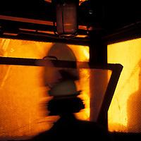 USA, Washington, Seattle, Worker silhouetted by glow of molten steel inside Birmingham Steel Plant