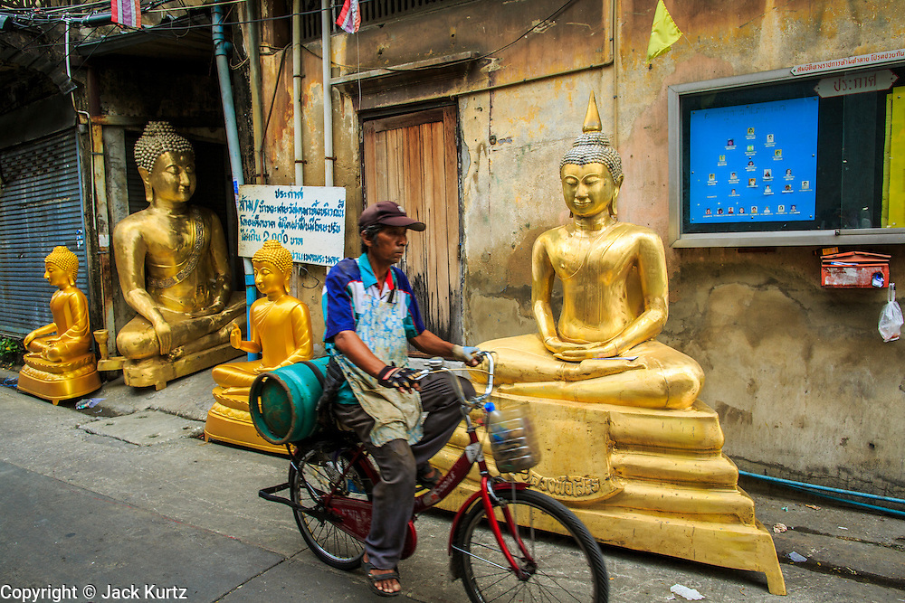 "12 NOVEMBER 2012 - BANGKOK, THAILAND:   A man bicycles past statues of the Buddha on Bamrung Muang Street in Bangkok. Thanon Bamrung Muang (Thanon is Thai for Road or Street) is Bangkok's ""Street of Many Buddhas."" Like many ancient cities, Bangkok was once a city of artisan's neighborhoods and Bamrung Muang Road, near Bangkok's present day city hall, was once the street where all the country's Buddha statues were made. Now they made in factories on the edge of Bangkok, but Bamrung Muang Road is still where the statues are sold. Once an elephant trail, it was one of the first streets paved in Bangkok. It is the largest center of Buddhist supplies in Thailand. Not just statues but also monk's robes, candles, alms bowls, and pre-configured alms baskets are for sale along both sides of the street.    PHOTO BY JACK KURTZ"