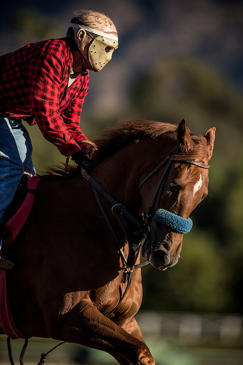 An Exercise rider wears a halloween mask while horses train for The Breeders' Cup at Santa Anita Park in Arcadia, California on October 31, 2013. (Alex Evers/ Eclipse Sportswire)