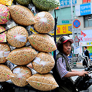 A delivery driver carries bags full of dried snack food on the back of a motorbike in Seoul, South Korea.
