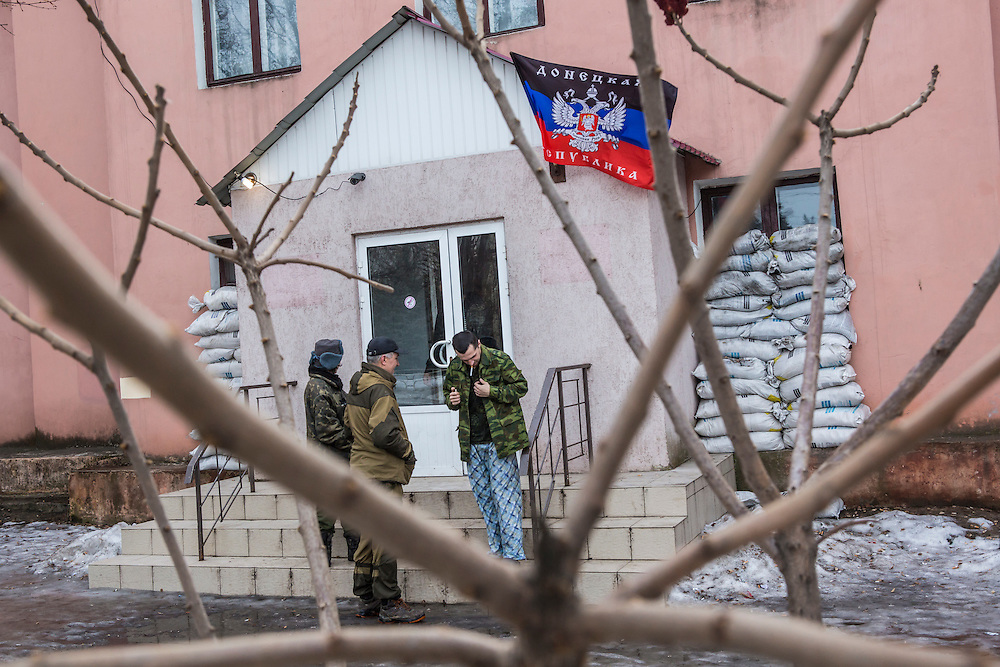 GORLOVKA, UKRAINE - JANUARY 31, 2015: Ira, left, and Batya, center, a rebel commander, greet a wounded comrade outside a hospital in Gorlovka, Ukraine. Fighting in Ukraine has intensified over the last week, with rebels declaring the end of a September ceasefire. CREDIT: Brendan Hoffman for The New York Times