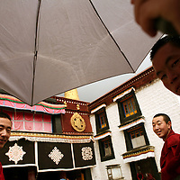 A Buddhist monk holds an umbrella as two other monks look on in front of the Jokhang Temple in Lhasa, the capital of Tibet in western China. (Photo/Scott Dalton)