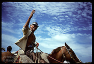 Rubber tapper waves adieu from atop his horse as he rides off to his family deep in jungle; Acre. Brazil